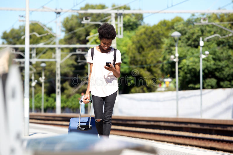 Young african woman walking on railway station with suitcase and mobile phone royalty free stock image