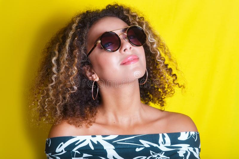 Portrait of a young afro american woman in sunglasses. Yellow background. Lifestyle. Portrait indoors of a young afro american woman in sunglasses. Yellow stock photo