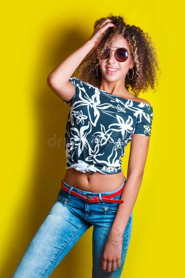 Portrait of a young afro american woman in sunglasses. Yellow background. Lifestyle. Portrait indoors of a young afro american woman in sunglasses. Yellow royalty free stock images