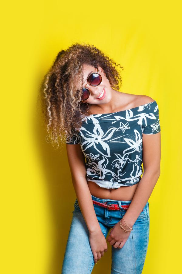 Portrait of a young afro american woman in sunglasses. Yellow background. Lifestyle. Portrait indoors of a young afro american woman in sunglasses. Yellow stock image