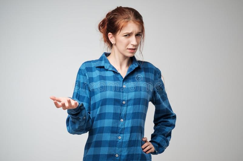 Portrait young angry woman in blue t-shirt. She is unhappy, annoyed by something. stock photography