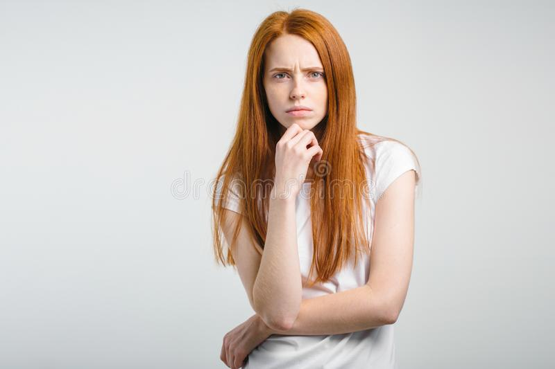 Female with freckles and pursed lips having disappointed unhappy look. Portrait of young annoyed female with freckles and pursed lips having disappointed unhappy royalty free stock photo