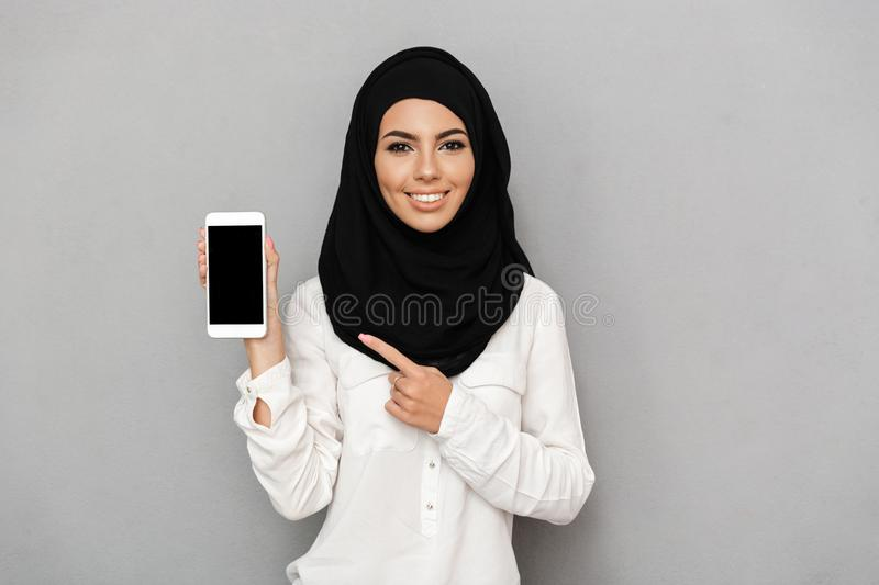 Portrait of young arab woman 20s in islamic headscarf with oriental makeup pointing finger on black screen of cell phone, isolate. Portrait of young arab woman stock image