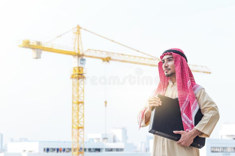 Portrait of young arabian businessman holding the briefcase and standing on construction site with crane background stock images