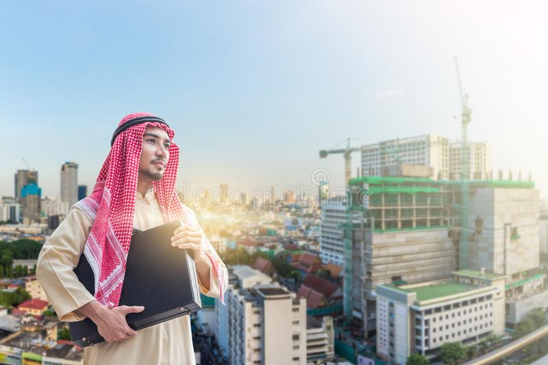 Portrait of young arabian businessman holding the briefcase and standing in downtown with commitment to success with building royalty free stock image