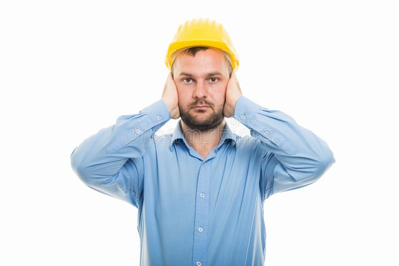 Young architect with yellow helmet covering ears stock photos