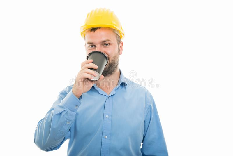 Portrait young architect with yellow helmet drinking coffee royalty free stock photography