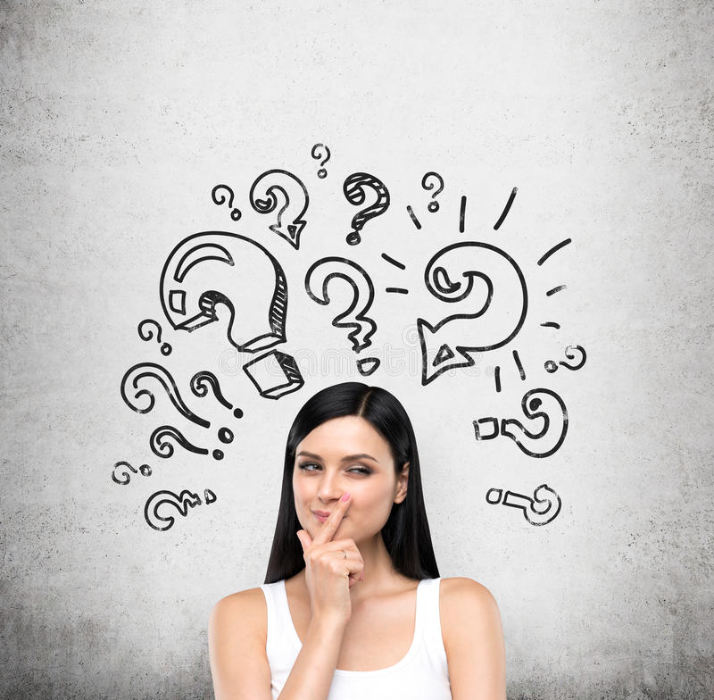 A portrait of a young artful brunette lady who is trying to find out a solution of some problem. The lady is in a white tank top. Different shapes of question stock photos