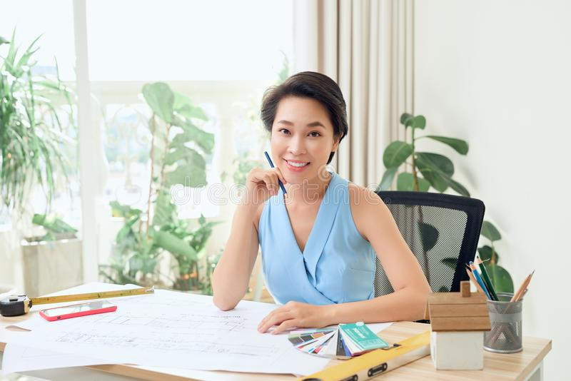 Portrait of young Asian architect sitting in her office royalty free stock image