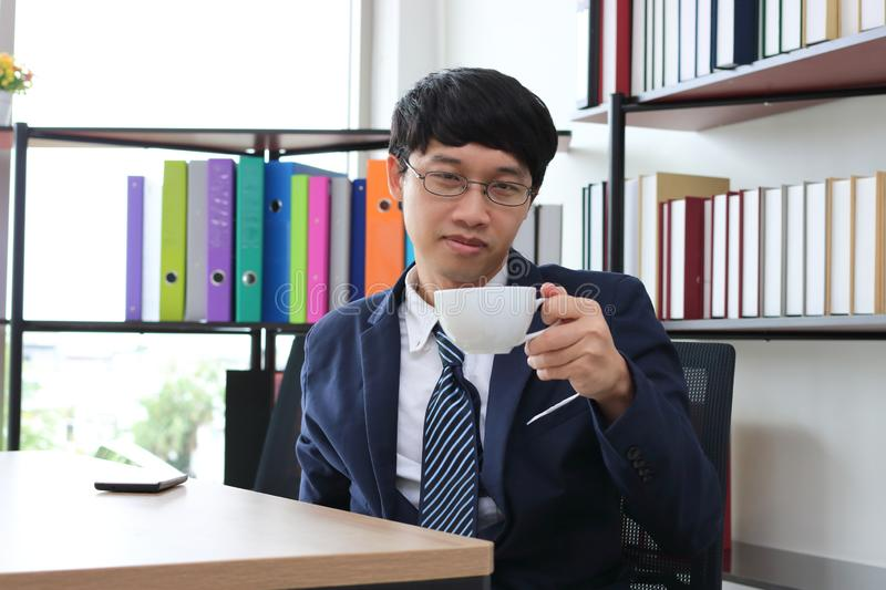 Portrait of young Asian business man in formal suit drinking coffee in office stock photos