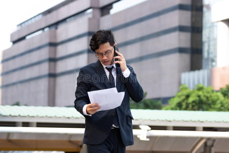 Portrait young Asian business man in suit analyzing charts or paperwork in hands outdoors stock images