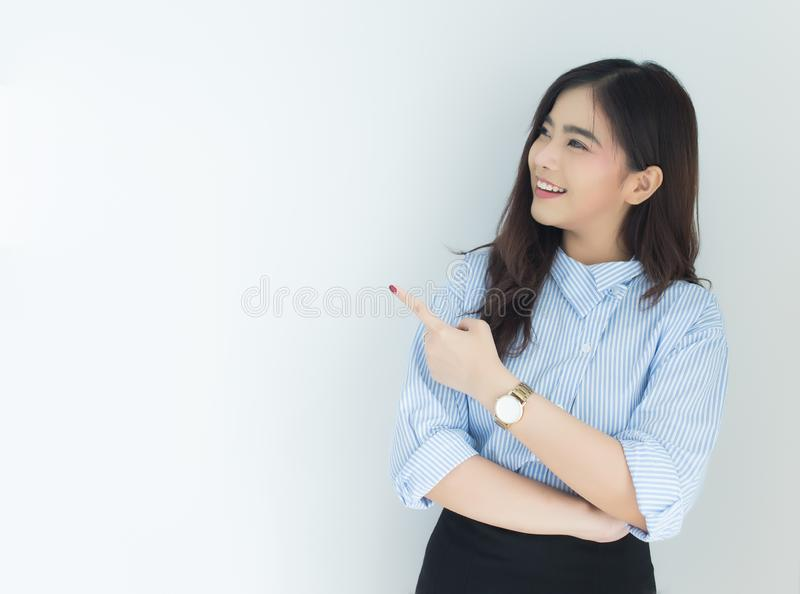 Portrait of young asian business woman pointing up over white background. royalty free stock photo