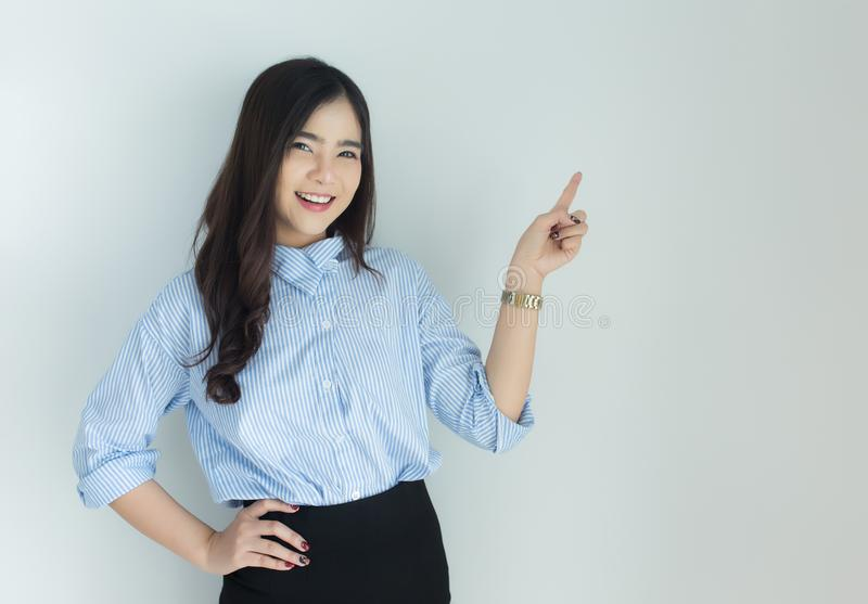 Portrait of young asian business woman pointing up over white background stock photos