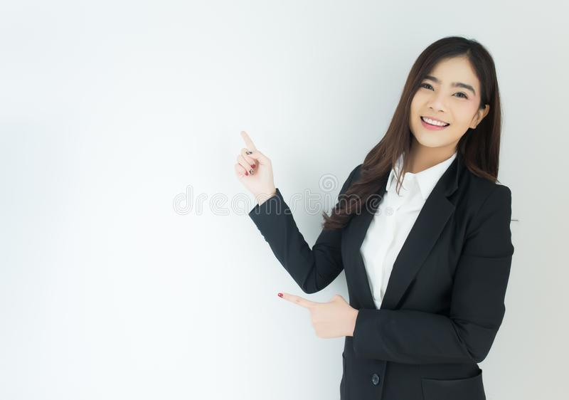 Portrait of young asian business woman pointing up over white background. stock images