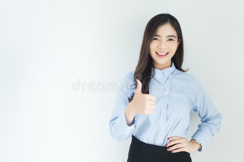 Portrait of young asian business woman thumbs up very good symbol on white background. royalty free stock images