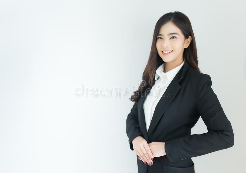 Portrait of young asian business woman welcoming gesture over white background. stock photo