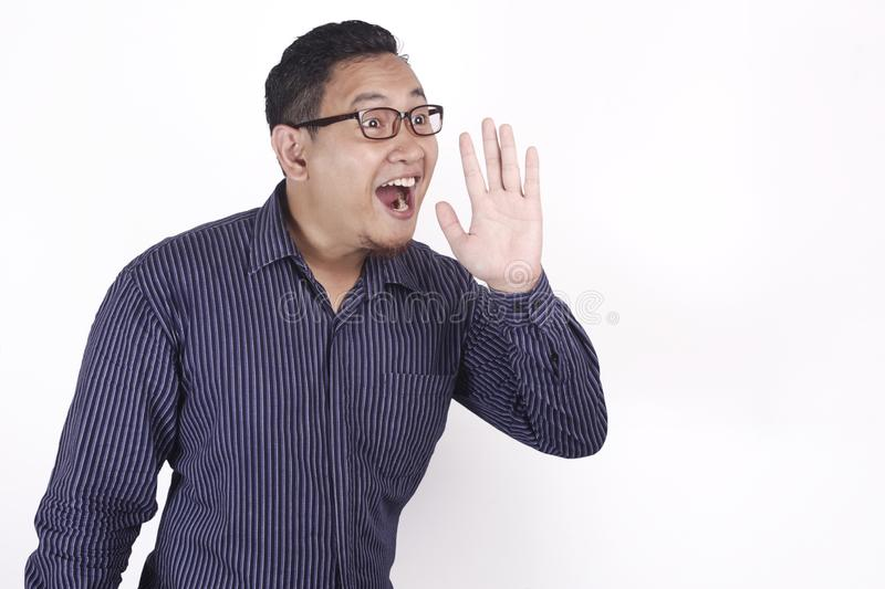 Young Man Speaking Out Loud. Portrait of young Asian businessman speaking out loud, against white background with copy space indonesian malaysian thai japanese royalty free stock image