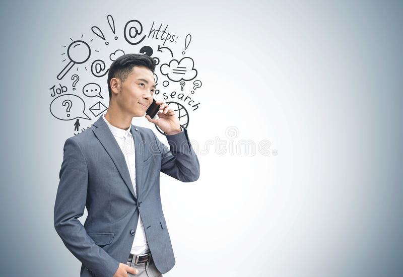 Asian businessman on phone, internet search stock image