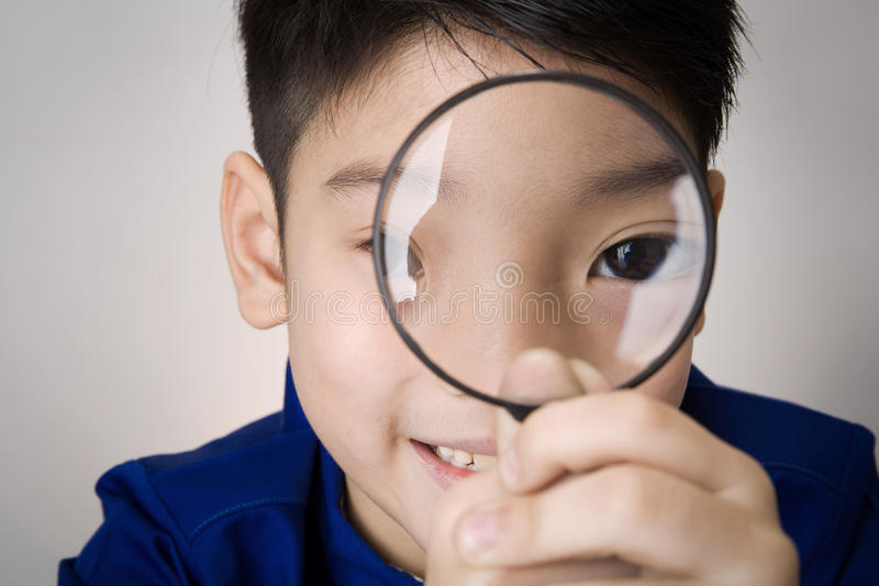 portrait of a young asian child looking through a magnifying glass stock photo
