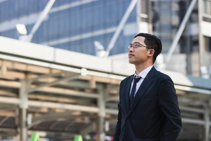 Portrait young Asian executive businessman in suit looking at far away outdoors. Business vision concept royalty free stock images