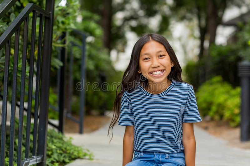 Portrait of a young Asian girl smiling outside. royalty free stock image