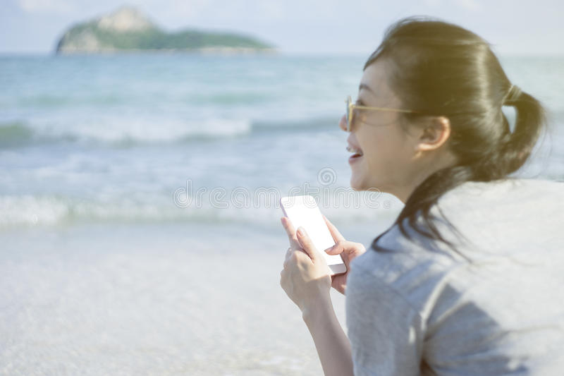 Portrait of young asian happy woman using smart phone at beach.technology concept.blurred beach sea background.clipping path royalty free stock images