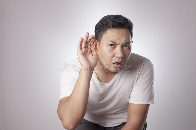 Man Listening Carefully, Hand on Ear. Portrait of young Asian man in casual white shirt hold his hand on ear trying to listening carefully to the conversation of royalty free stock image