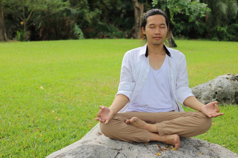 Portrait of young Asian man doing yoga meditation while sitting in lotus position on the rock in beautiful outdoor park. Portrait of young Asian man doing yoga stock photo
