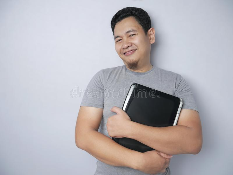 Asian Man Holding Laptop and Smiling stock image