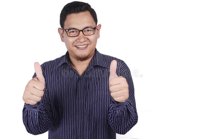 Young Man Shows Thumbs Up. Portrait of young Asian man shows thumbs up sign, happy smiling person, OK deal concept, indonesian, malaysian, thai, male, adult royalty free stock images