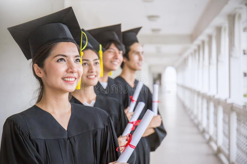Portrait of young asian man and woman graduates standing in line. Portrait of young asian men and women graduates standing in line in front of university royalty free stock images