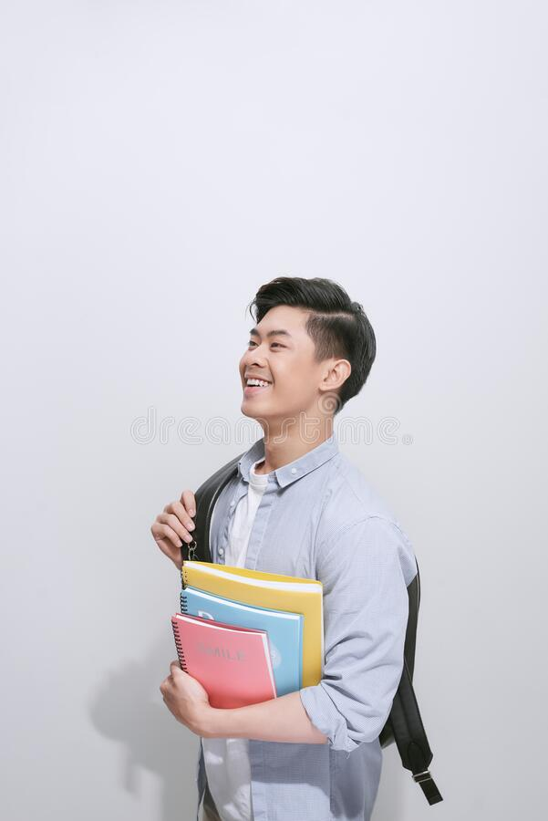 Portrait of young asian student holding books isolated over white background.  stock images
