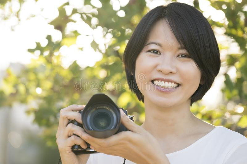 Portrait young Asian woman with camera royalty free stock image