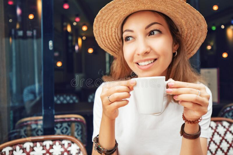 Young Asian woman drinking coffee in a cafe. Focus on white cup. Portrait of young Asian woman drinking coffee in a cafe. Focus on white cup stock photography