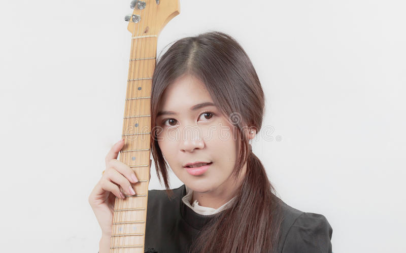 Portrait of young Asian woman enjoys playing guitar. royalty free stock images