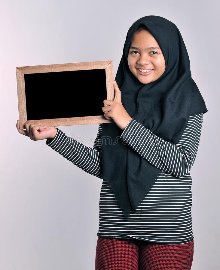 Portrait of young asian woman in islamic headscarf holding chalkboard. Smiling asian woman wearing  islamic headscarf holding stock photos