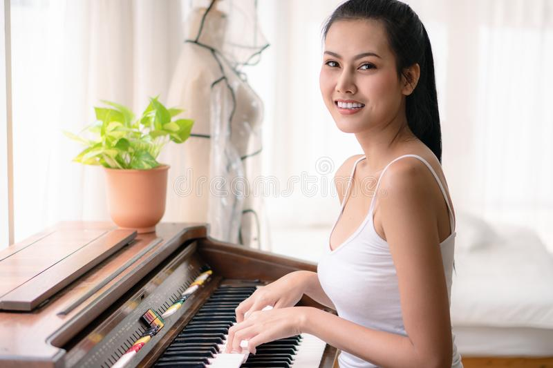 Portrait of young asian woman playing piano in living room at home royalty free stock photography