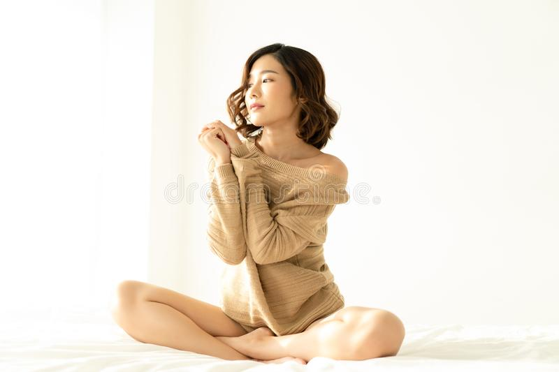 Portrait of young Asian woman smiling friendly wearing knitted warm sweater and looking away to window in bed room. Concept woman stock images