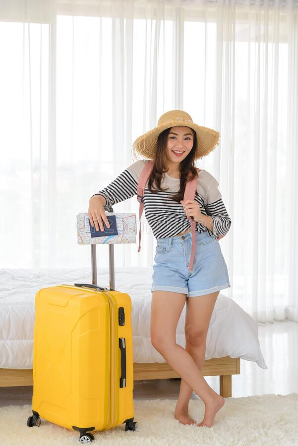 Portrait of young Asian woman in summer casual clothes and hat is smiling and relaxing mood with her yellow baggage in her bedroom royalty free stock photography