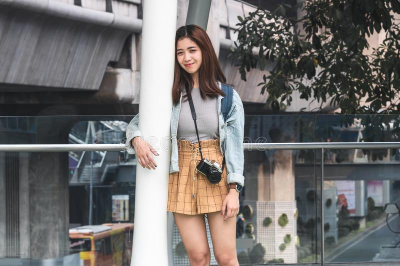 Portrait of young Asian woman tourist leaning against a pole outdoors in urban. Travel and vacation concept royalty free stock photos