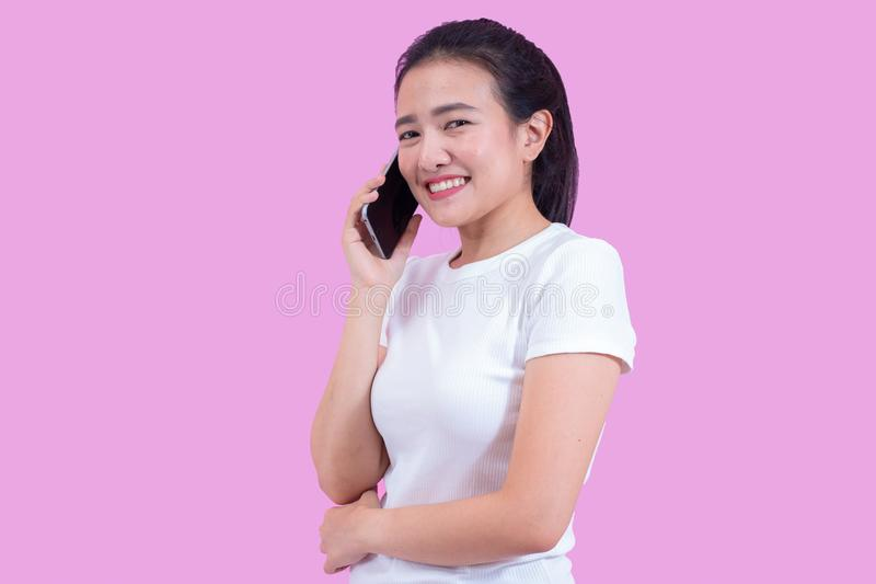 Portrait of young asian woman wearing white shirt successful talking phone call on smartphone and happy smile isolated stock photography