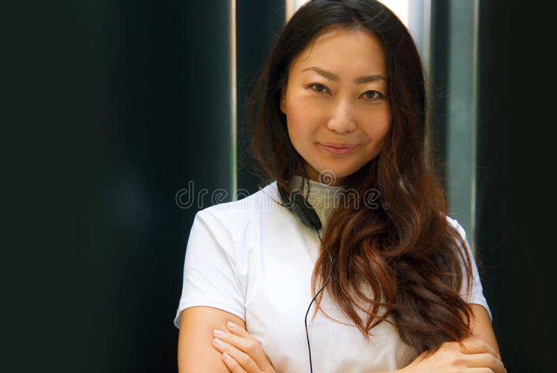 Portrait of a young asian woman in white with headphones listening to music with her smartphone. Closeup portrait of a young asian woman in white with stock photo
