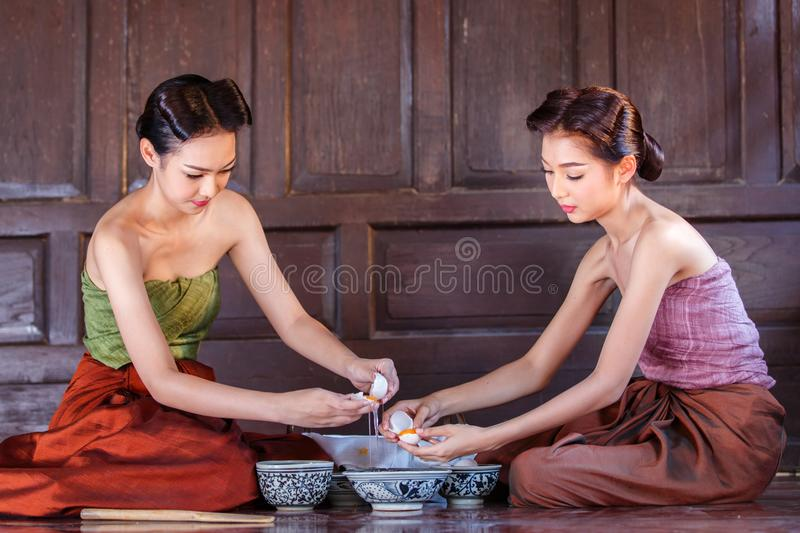 Portrait young asians women dressed in ancient Thailand are helping to make the dessert thai of Thai culture royalty free stock images
