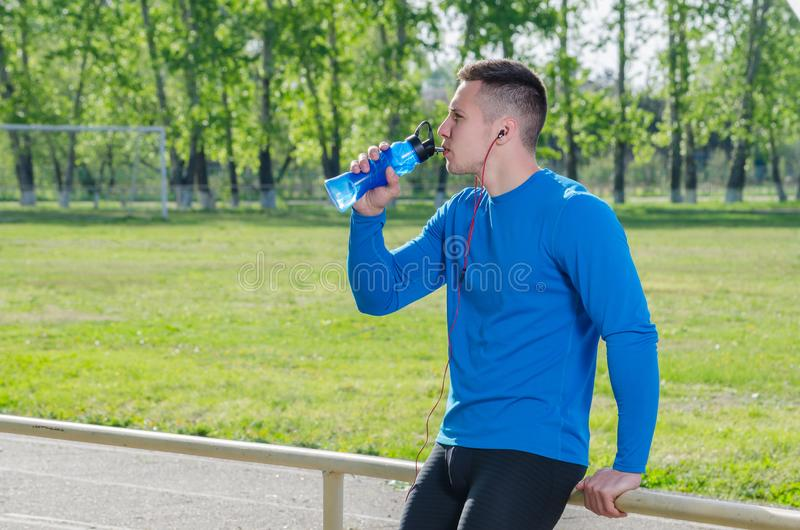 Portrait of a young athlete in headphones drinking water royalty free stock photos