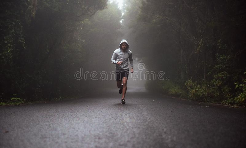 Portrait of a young athlete running on the road stock photo