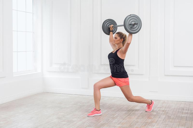 Portrait of young athletic beautiful bodybuilder woman in pink shorts and black top holding barbell over head and doing squats stock images