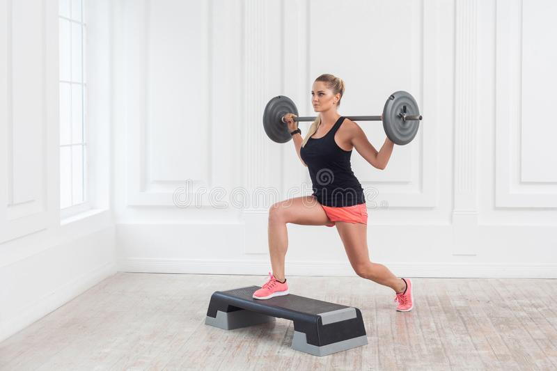 Portrait of young athletic beautiful bodybuilder woman in pink shorts and black top holding barbell on shoulders and doing squats royalty free stock image
