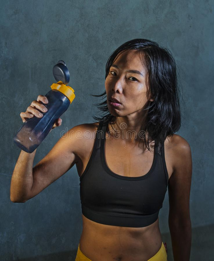 Portrait of young athletic and fit Asian Korean woman in fitness top holding drinking water bottle posing cool in bad girl defiant royalty free stock image