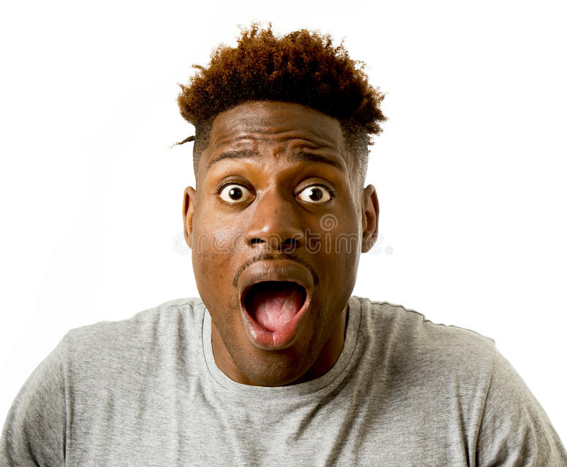 Portrait of young attractive afro american man surprised with opened mouth and wide open eyes royalty free stock photography
