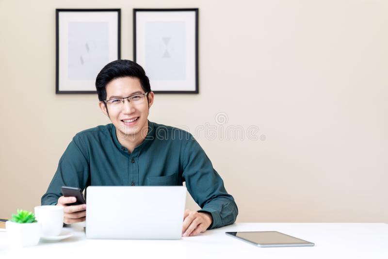 Portrait of young attractive asian businessman or student using mobile phone, laptop, tablet, drinking coffee sitting on desk royalty free stock image